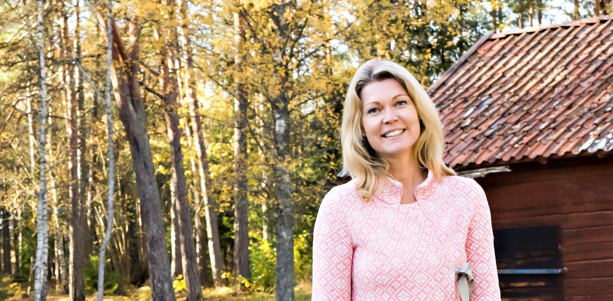 Anna Wiklund står framför skog och en röd stuga.
