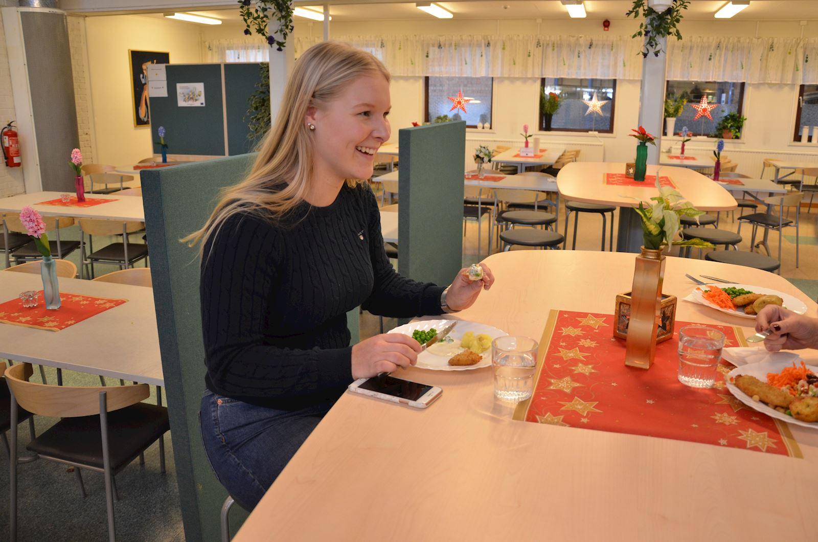 Linda Westerlund sitter vid ett bort och äter mat.